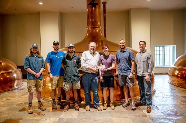 When kindred spirits come together, it's all smiles. Members of the Only in Wisconsin Giving, Inc. Charitable Foundation present a $25,000 check to Ice Age Trail Alliance staff. Standing left to right in front of an enormous kettle of New Glarus Brewing Company brew is Ciaran O'Neill-Culhane, Eric Felt, Riley Miller, Mike Wollmer, Kari Haser, Luke Kloberdanz, and Drew Cochrane. Photo by Susan Moen.
