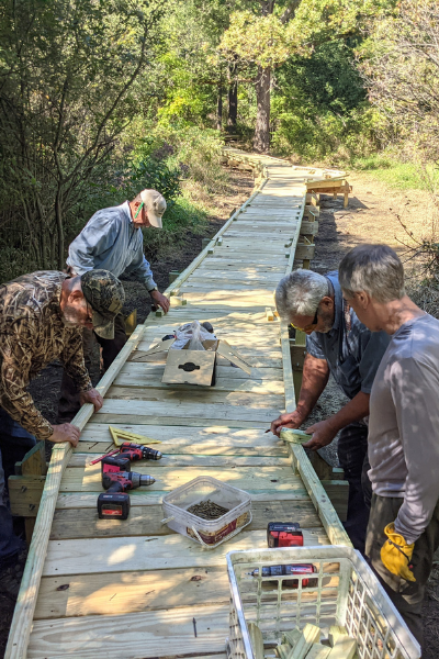 Volunteers carefully measuring out pieces for the edge of the boardwalk. Photo by Dave Caliebe.